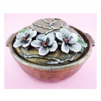 Brownish Colored Clay Pot With Colored Protruding Leaves And Flowers